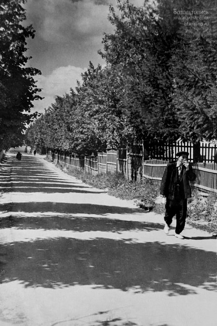 На пешеходной дорожке у школы №3, на заднем плане старый забор школы. Раньше проезжая дорога шла вровень с пешеходной, 1950-е годы