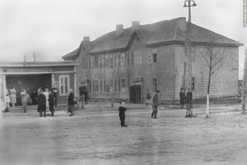 Сейчас на месте этого деревянного дома стоит дом №15 по пр. Ленина, павильон ожидания автобусов находился на южной стороне улицы, 1950-е годы